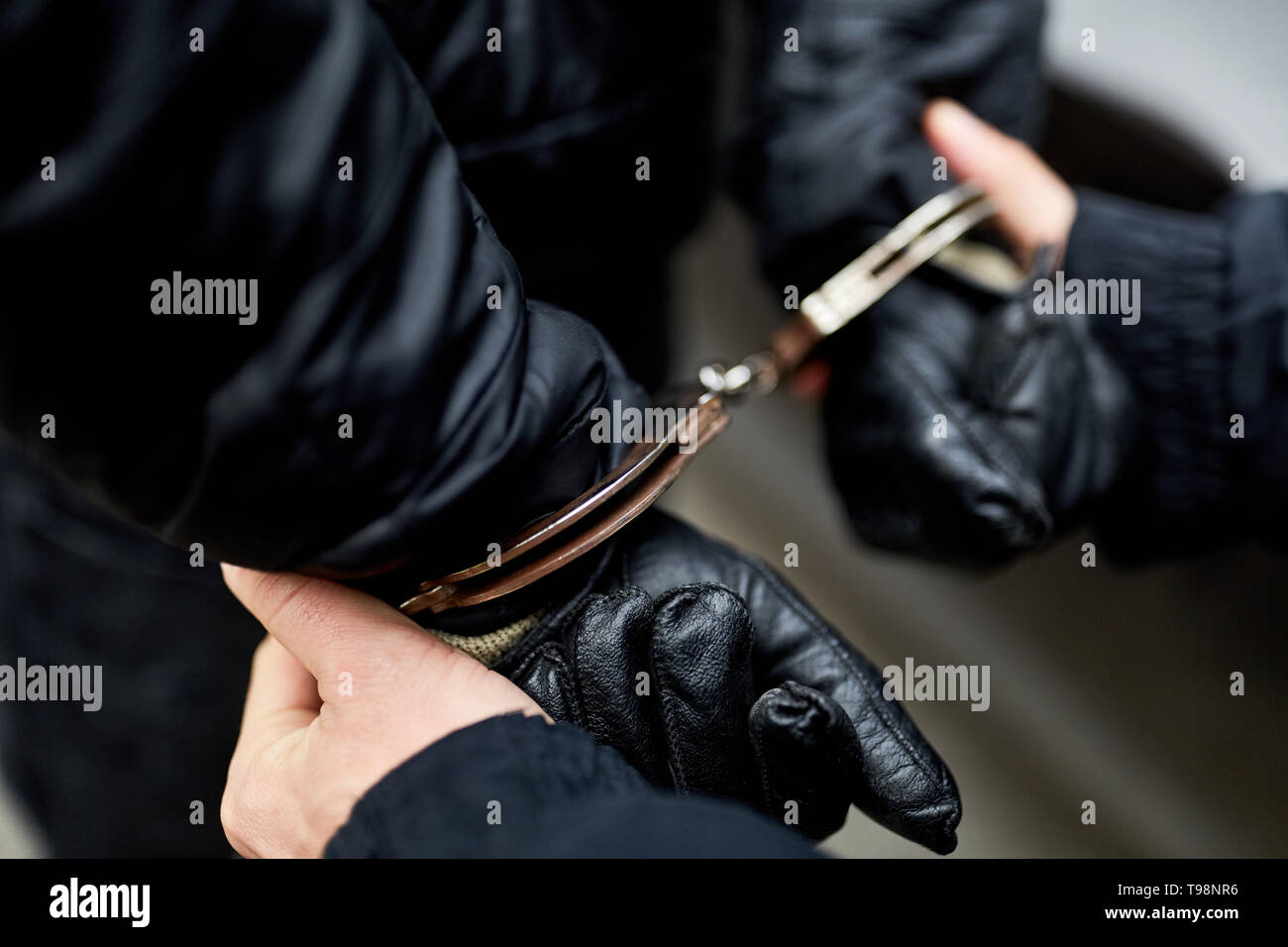 Hands handcuffed behind the back of police at arrest - Stock Image
