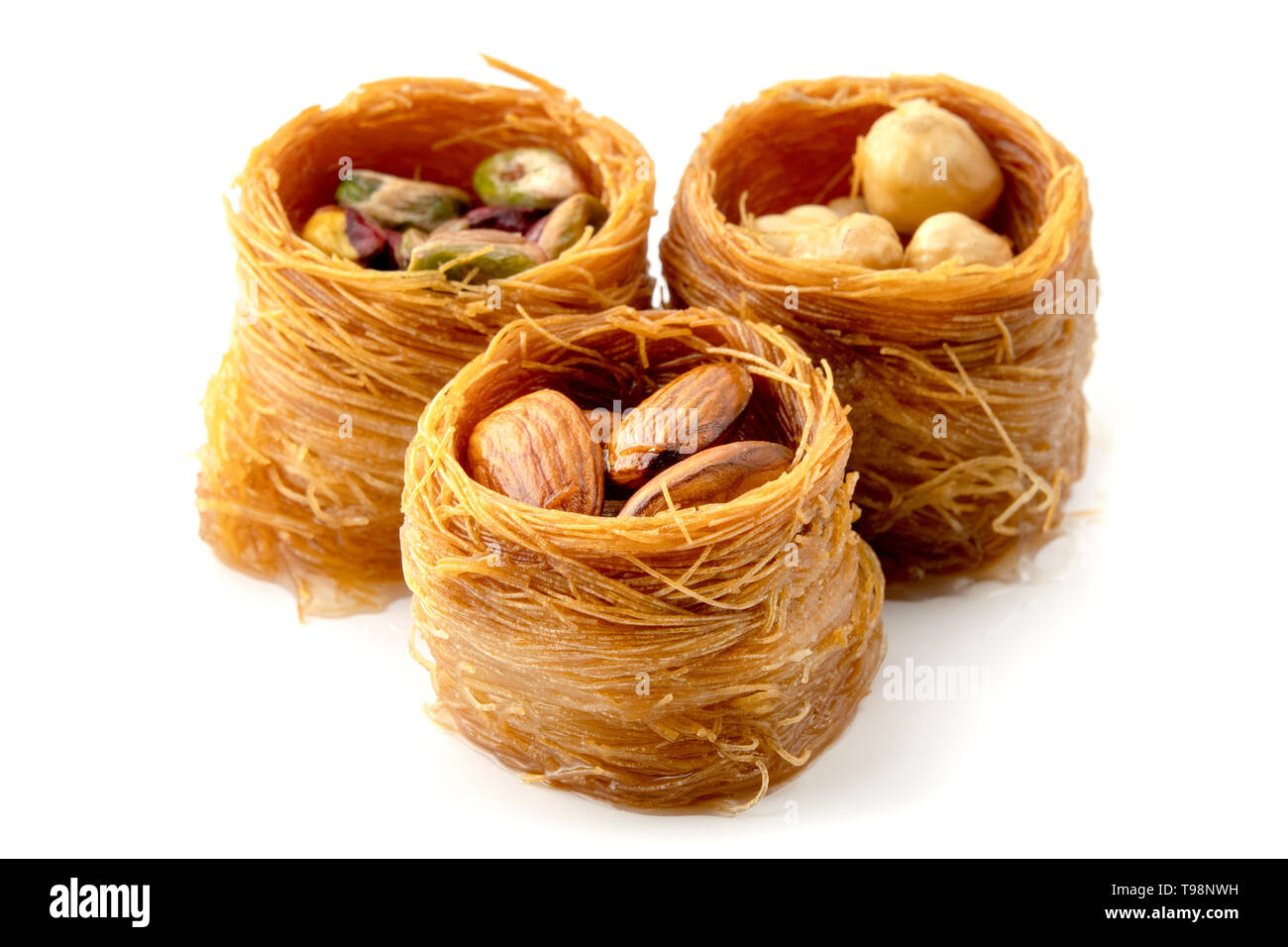 Mixed Bird nest baklava with almonds, nuts and pistachios on a white background - Stock Image