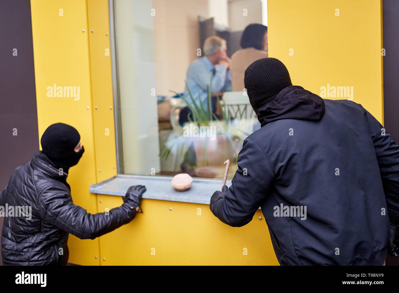 Burglars peek residents through a window from the house before a burglary - Stock Image