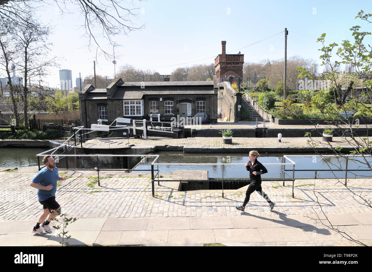 People jogging by St Pancras Lock with Lock Keepers Cottage and Waterpoint in the background, Regent's Canal, Grand Union Canal, London, England, UK - Stock Image
