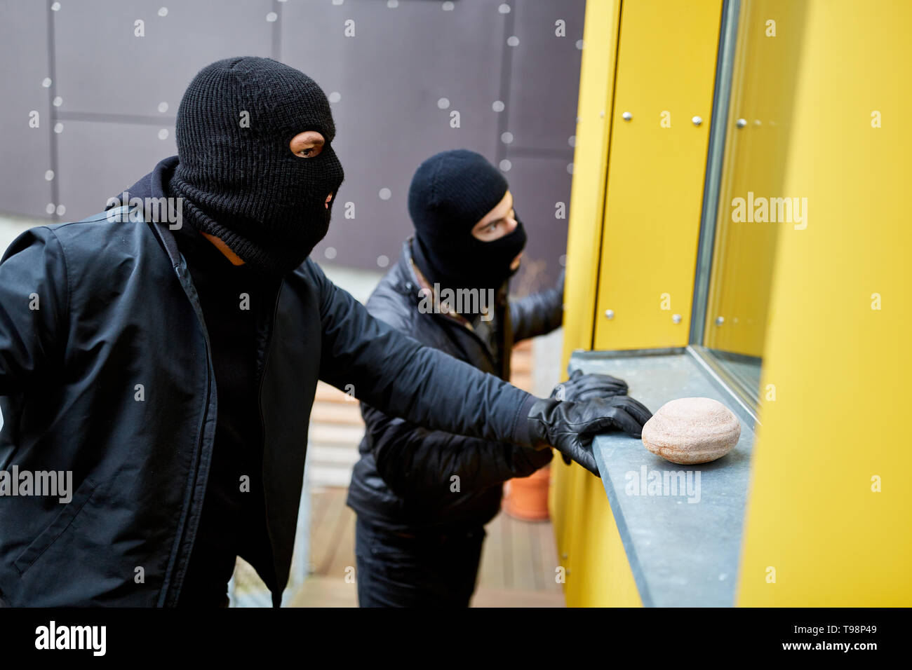 Two burglars watch the window of a detached house - Stock Image
