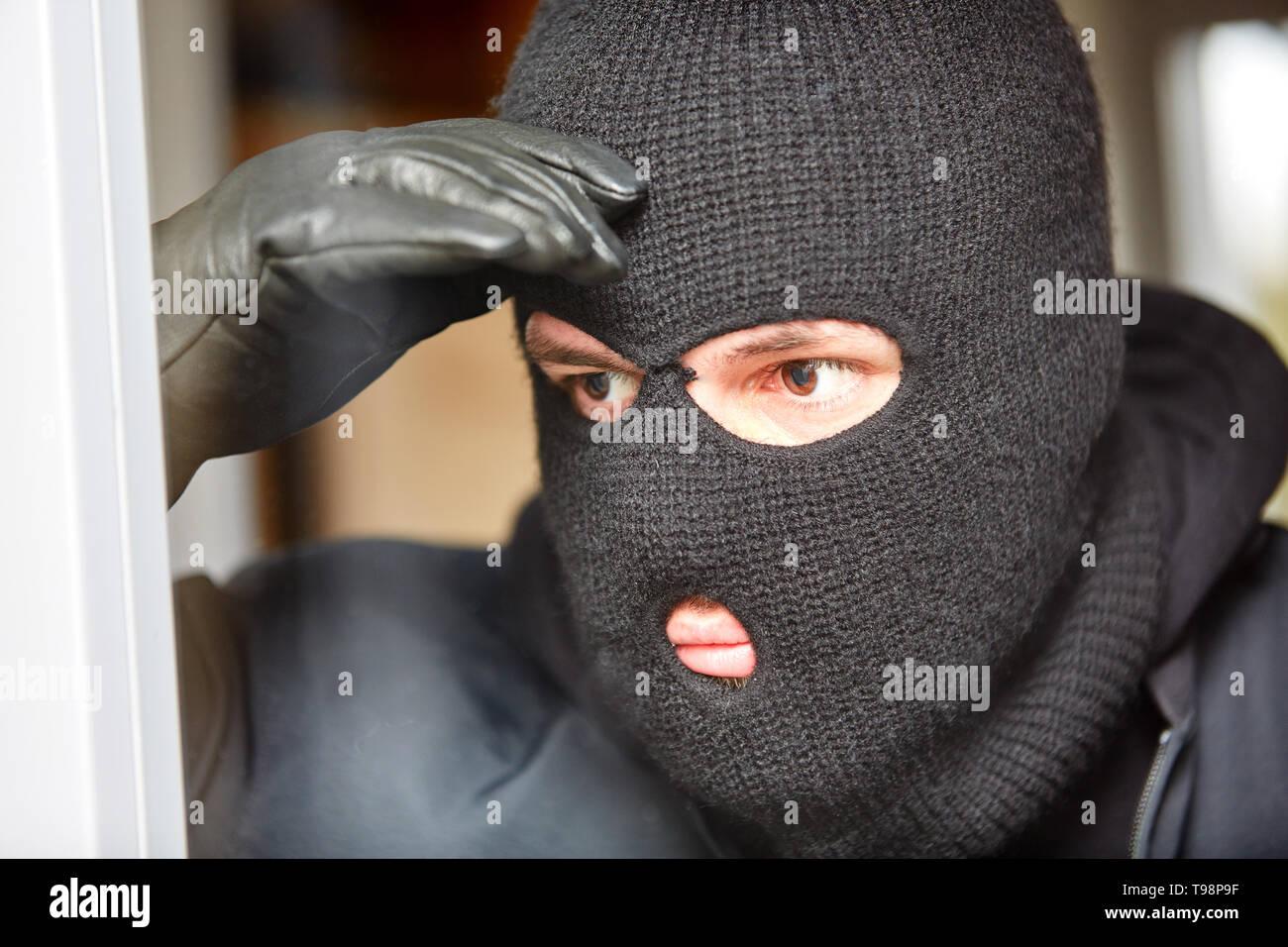 Masked burglar with balaclava peeks through window of a house before a burglary - Stock Image