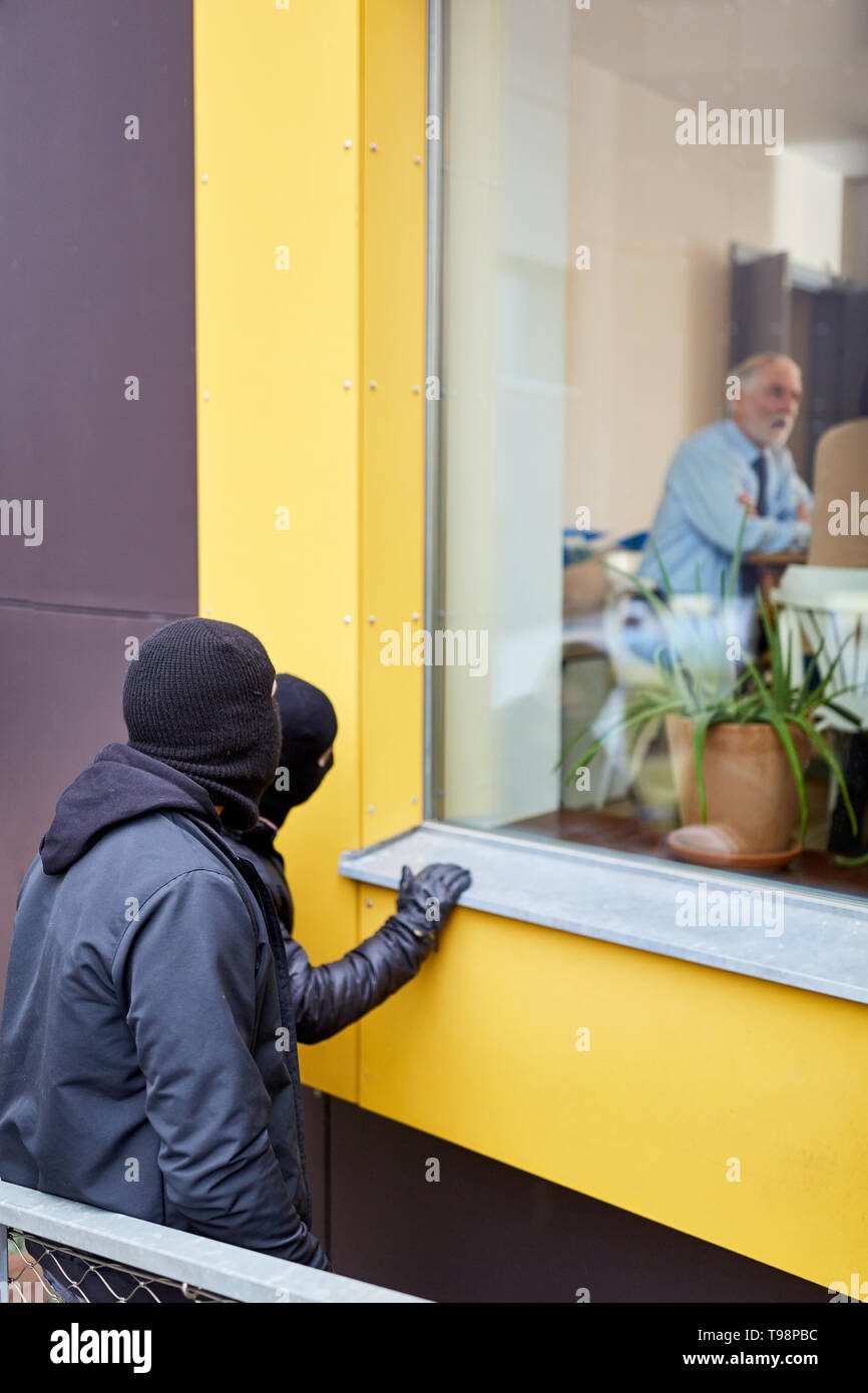 Burglars watch residents of the house from a burglary - Stock Image