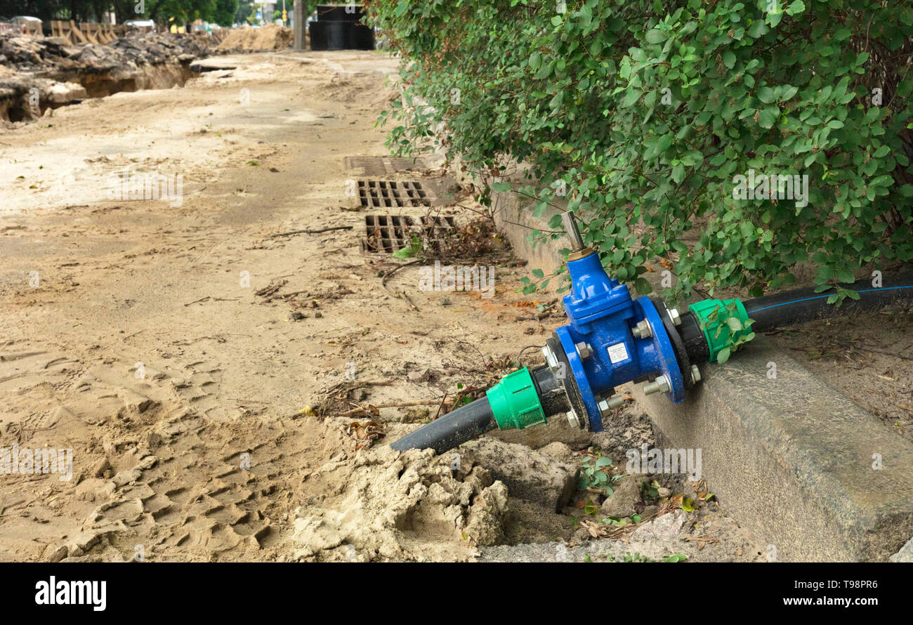 Water resistant water gate valves near the grilles of city stormworks near the excavated trench on the roadway of the street - Stock Image