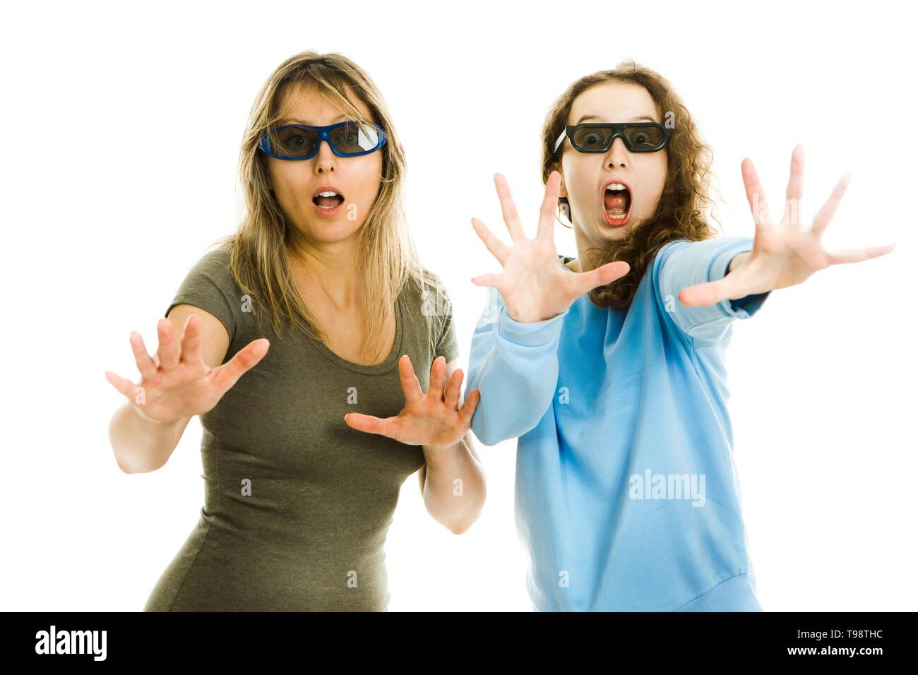 Amazed woman and girl in cinema wearing 3D glasses experiencing 5D cinema effect - scared watching performance - gestures of astonishment - concept on - Stock Image