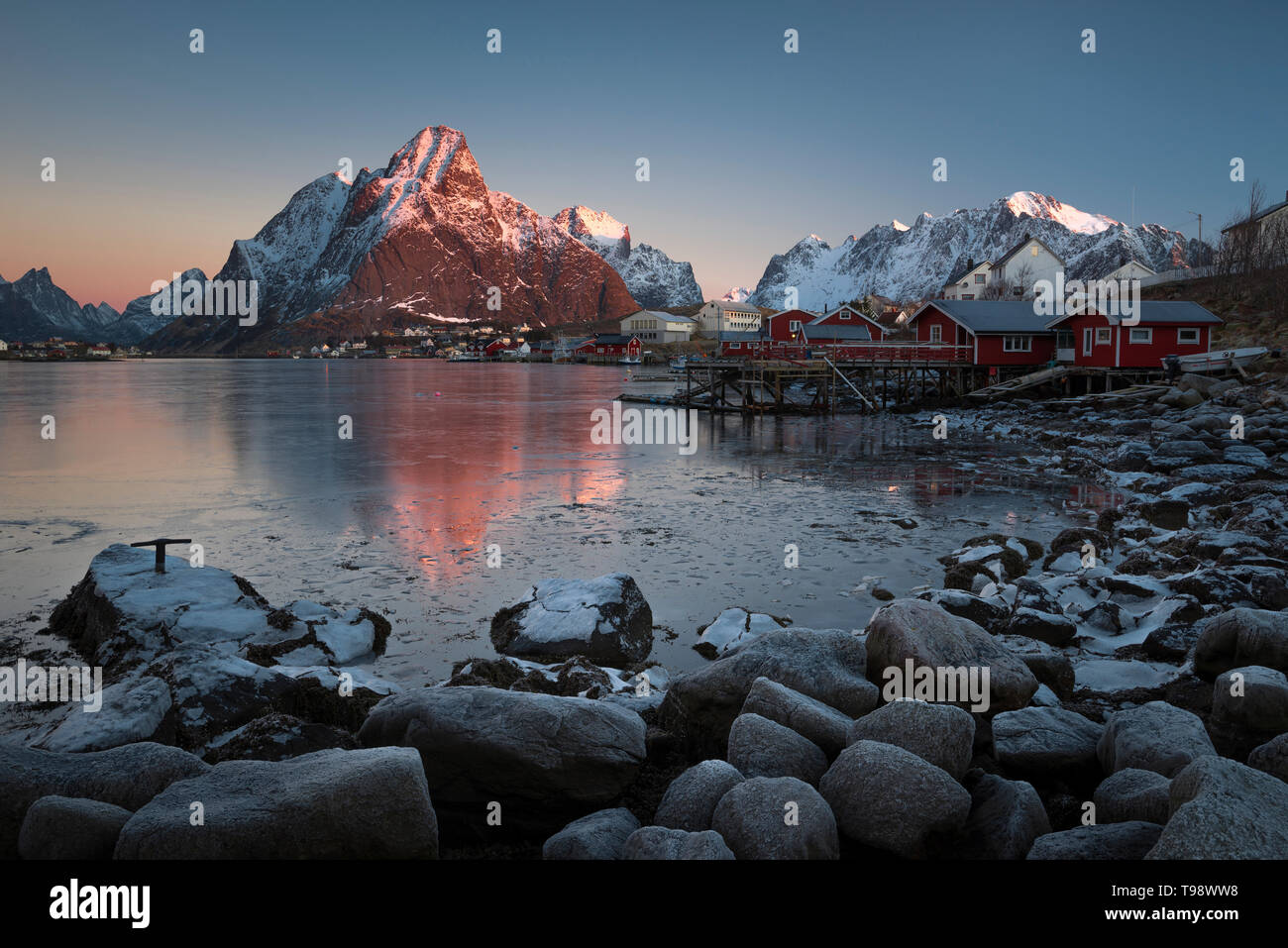 Morning light illuminates the snow-covered Olstinden in the fishing village Reine, Reine, Nordland, Norway Stock Photo