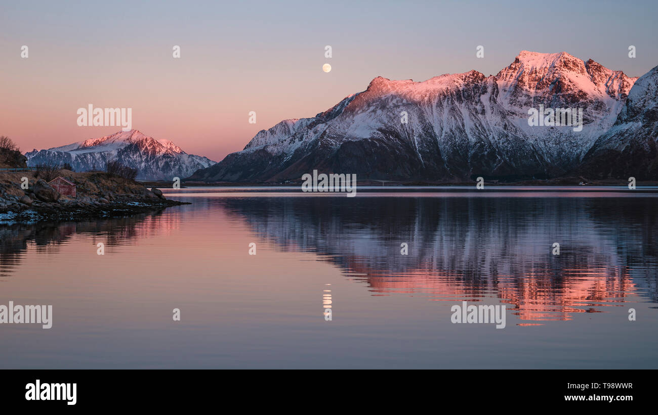Mountain peaks in the evening light reflect together with the full moon in the water, Lofoten, Nordland, Norway - Stock Image