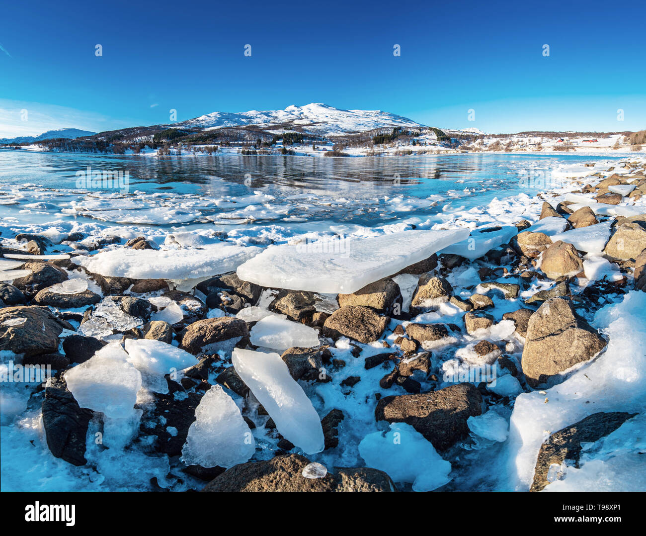 Wide angle view of beautiful winter lake with ice on the coast at Lofoten Islands in Northern Norway - Stock Image