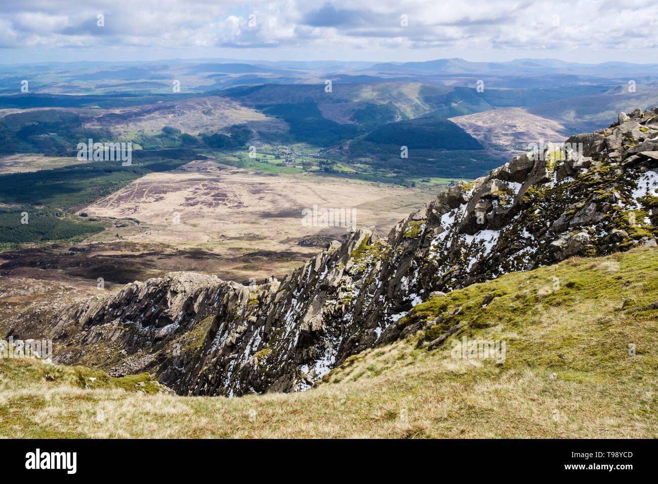 Looking down Daear Ddu rocky east ridge rock scramble with bits of snow and hikers on Carnedd Moel Siabod mountain in Snowdonia National Park Wales UK - Stock Image