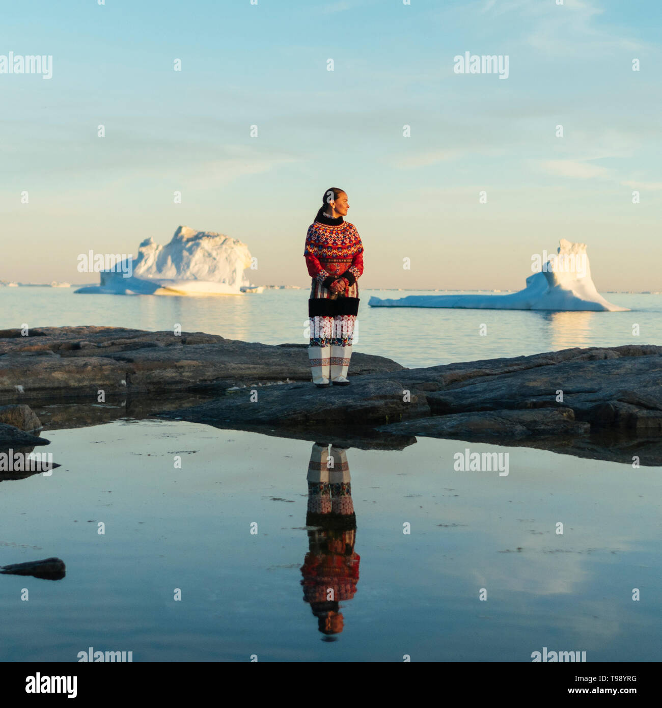 Inuit woman in traditional clothes stands on the shore of Disko Bay on Midsummer, Greenland - Stock Image