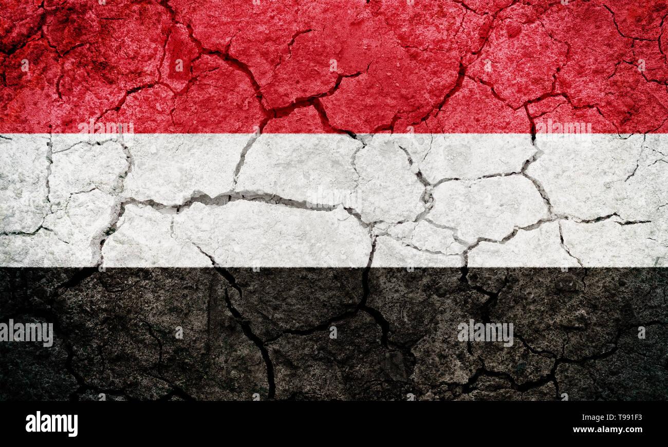 Republic of Yemen flag on dry earth ground texture background - Stock Image