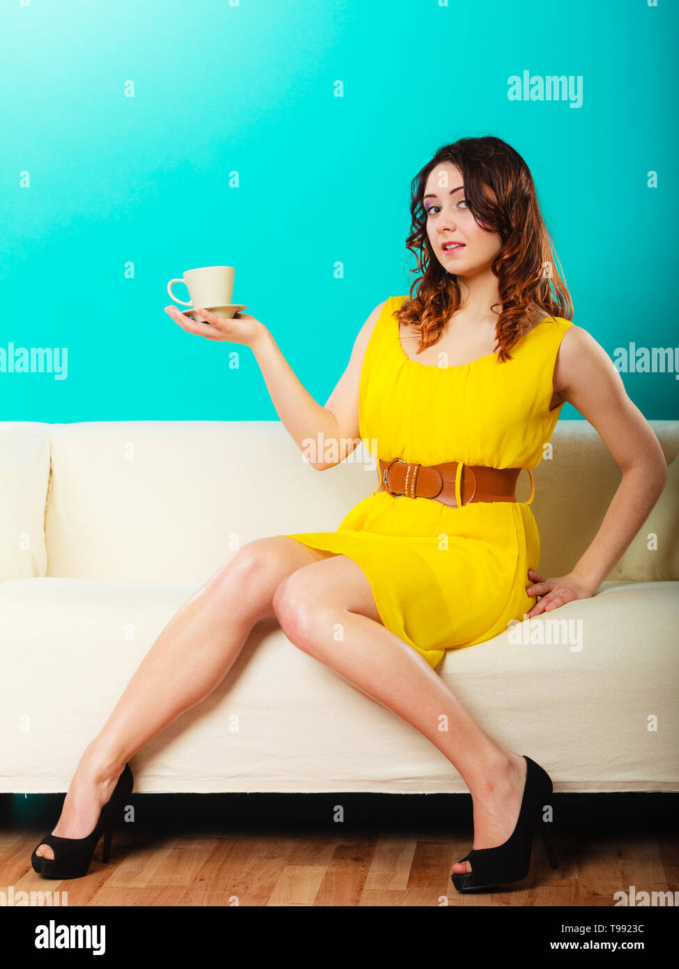 Beauty fashion and relax concept. Fashionable girl yellow dress holding hot drink coffee or tea cup, sitting on sofa - Stock Image