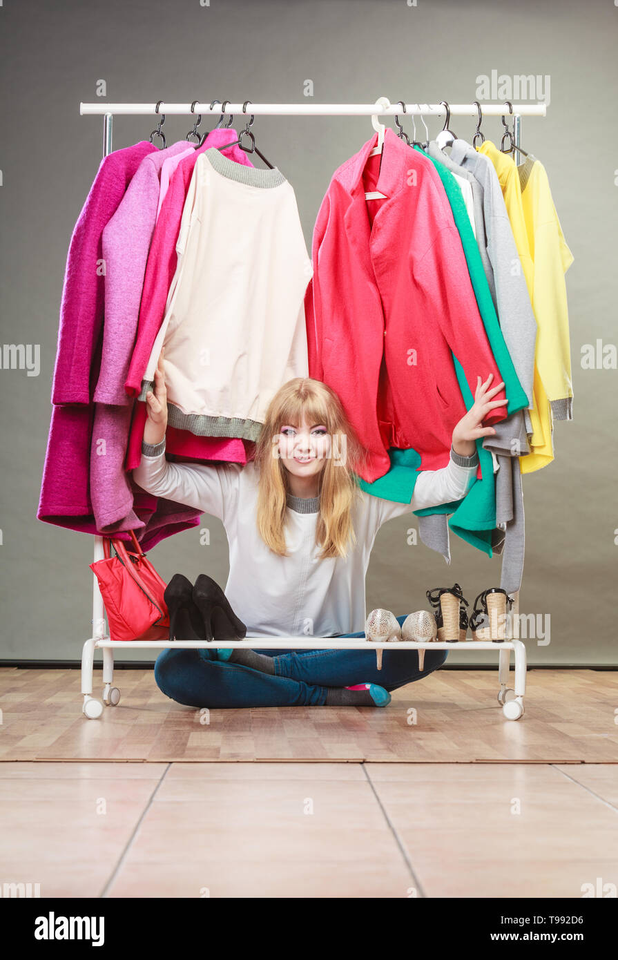 Pretty woman sitting under clothing from wardrobe. Young happy undecided shopper girl bought new clothes. Shopaholic concept. - Stock Image