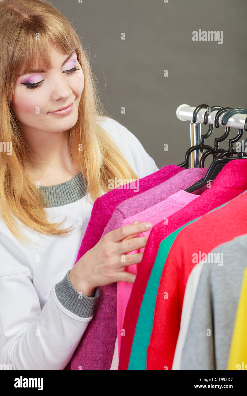 Pretty happy woman choosing which clothing wear from wardrobe. Young undecided shopper girl bought new clothes. Shopping sale concept. - Stock Image
