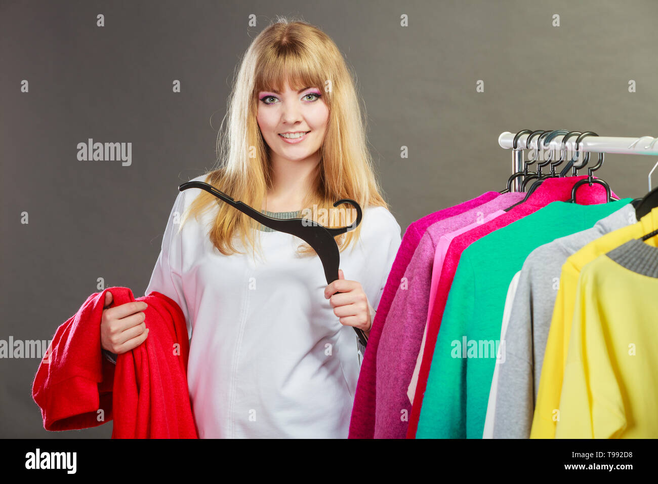 Pretty happy woman with hanger in hand choosing which clothing wear from wardrobe. Young undecided shopper girl bought new clothes. Shopping sale conc - Stock Image