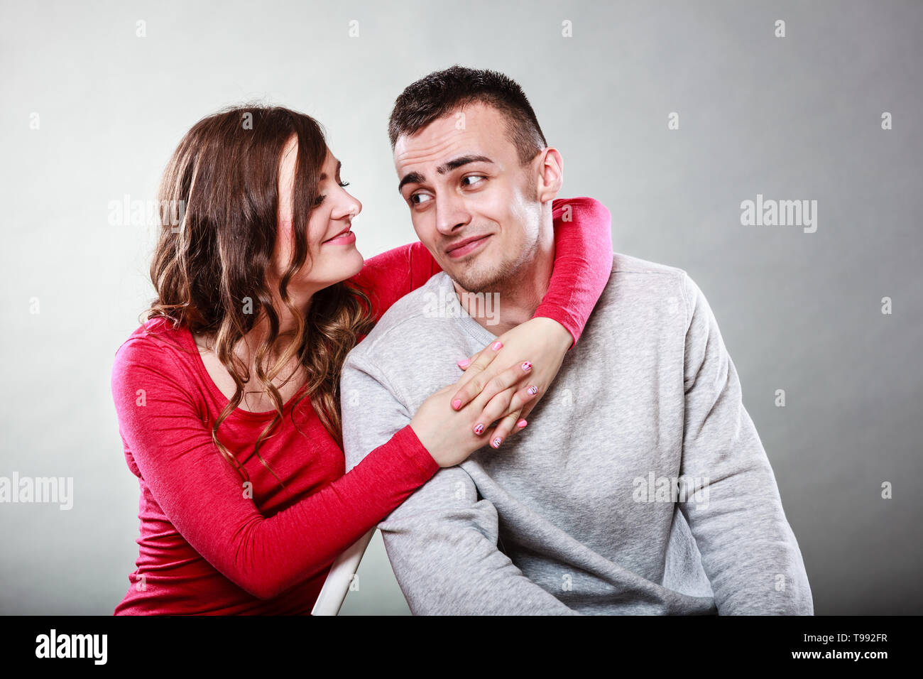 Happy smiling young couple hugging embracing. Joyful man and woman having nice time. Love. Good relationship. - Stock Image