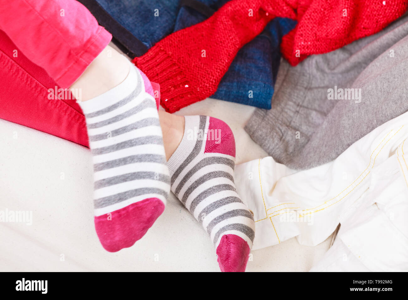 Close up of human woman feet in colorful striped socks. - Stock Image