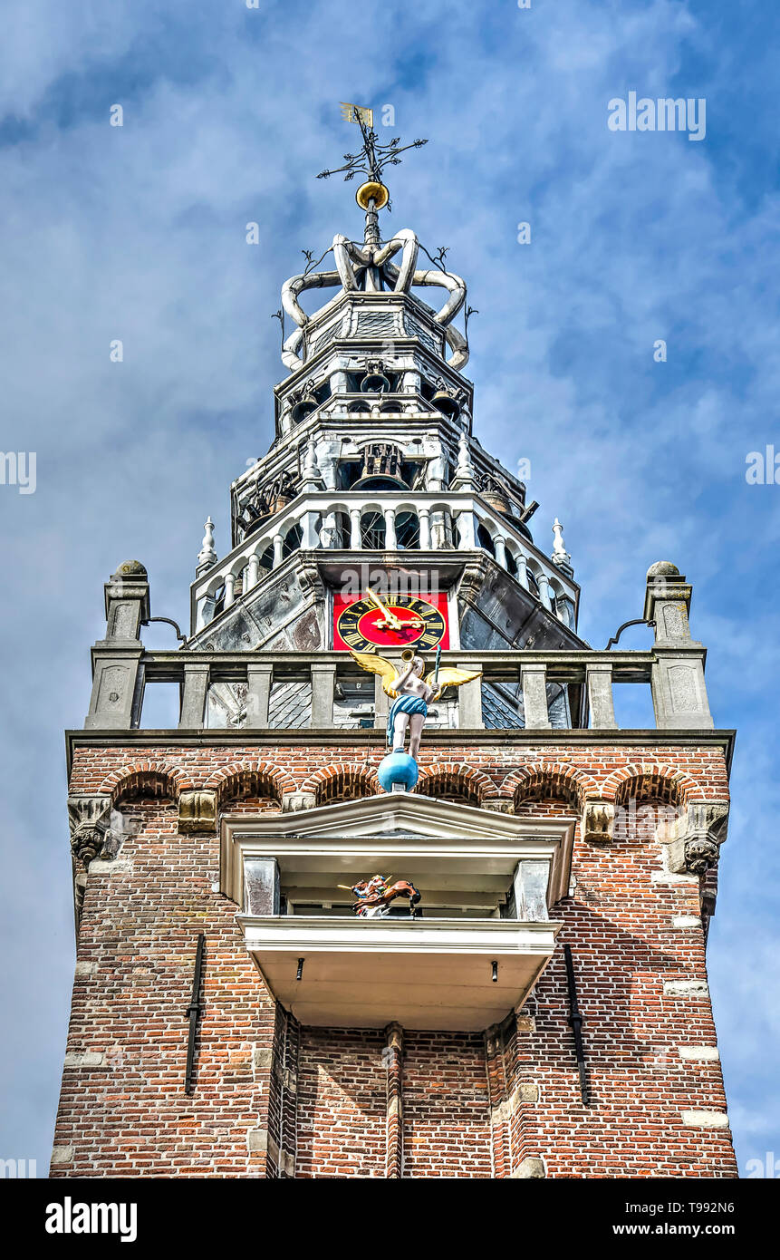 Monnickendam, The Netherlands, October 7, 2018: view from below of the tower of the town hall, with clock, carillon and ornaments against a partially  - Stock Image
