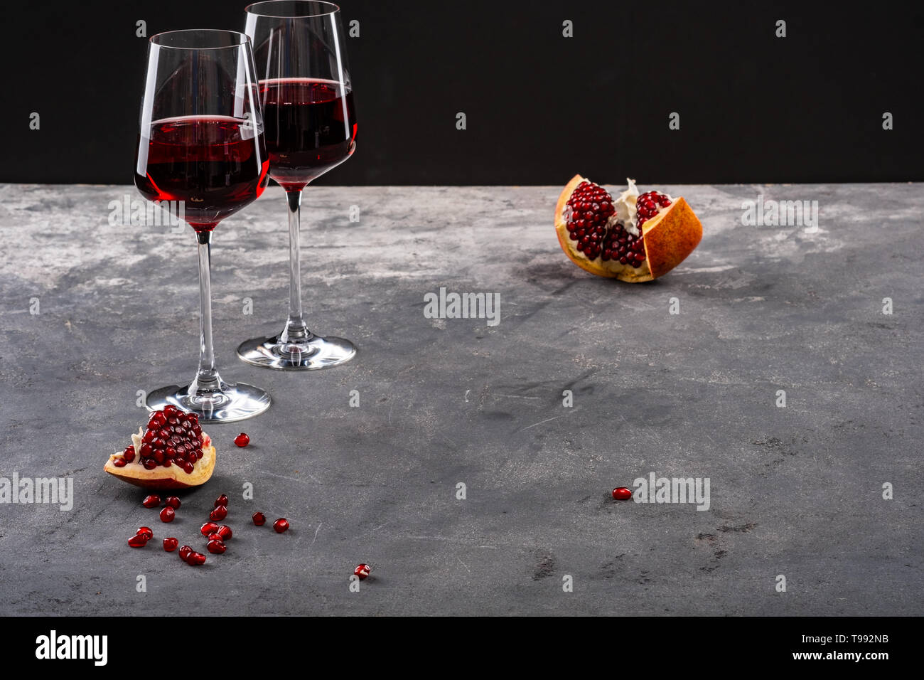 Red garnet, pomegranate and garnet red wine. Two glasses. Copy space - Stock Image