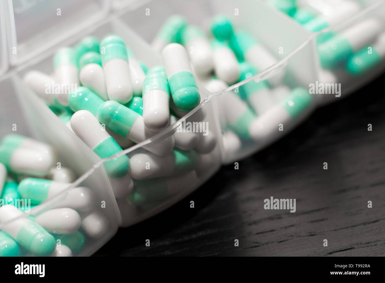 Extreme close up of seven day pill box with pills. Blu pill-box with tuesday pills visible. Open pill box on black background - Stock Image