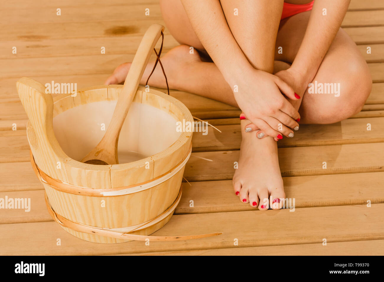 Closeup of human woman legs feet, hands with sauna bucket and ladle. Person relaxing resting in spa. - Stock Image