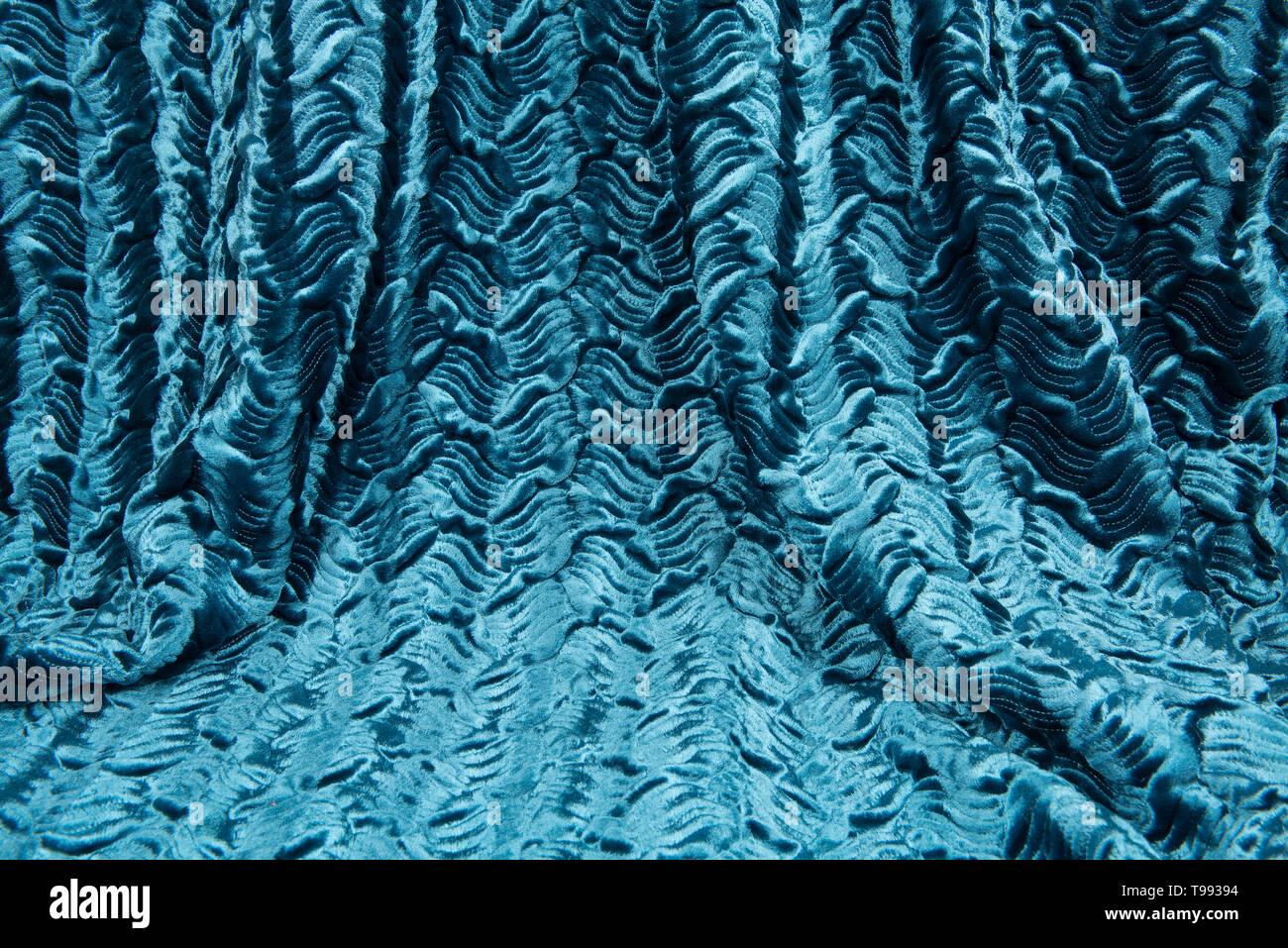 Full frame teal blue luxury shiny draped curtain - Stock Image