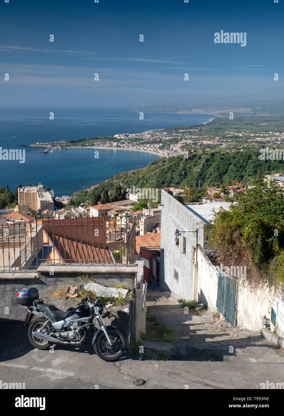 View over the roof tops to the Bay of Naxos, Taormina, Sicily. - Stock Image