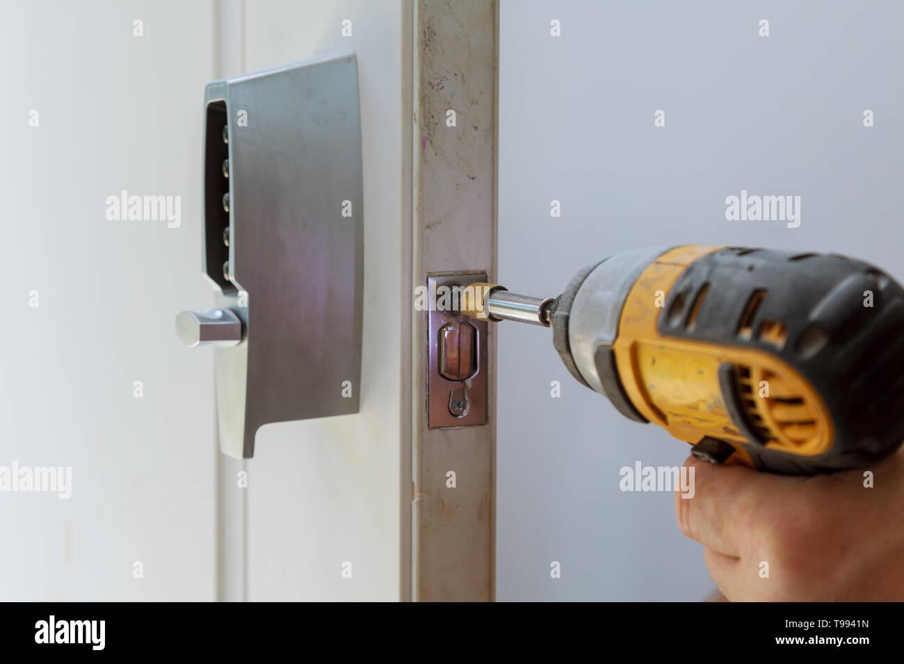 Rear view of repairman installing of the door lock electronic key - Stock Image
