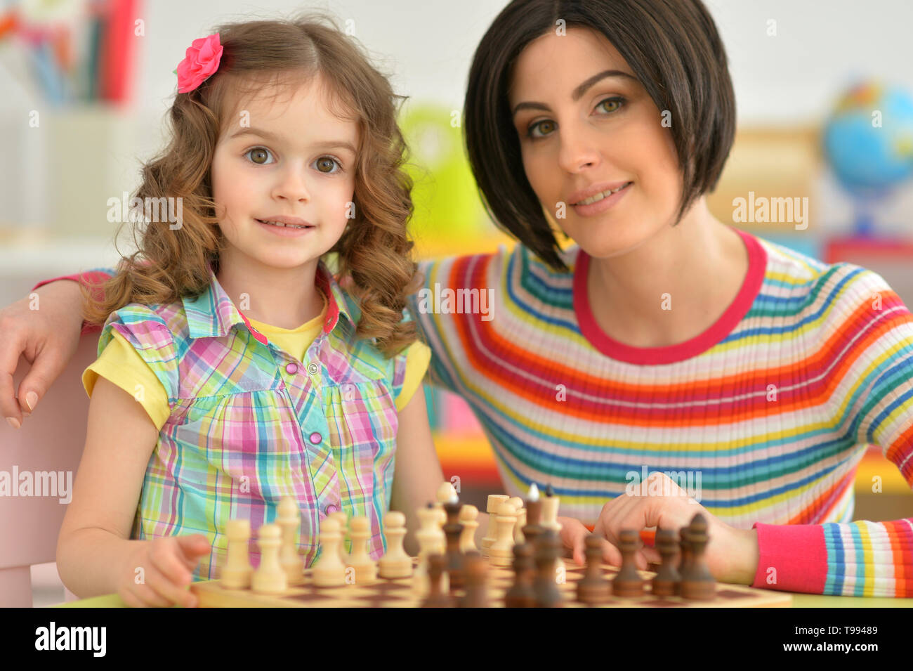 Beautiful young mother with her cute little daughter playing chess - Stock Image