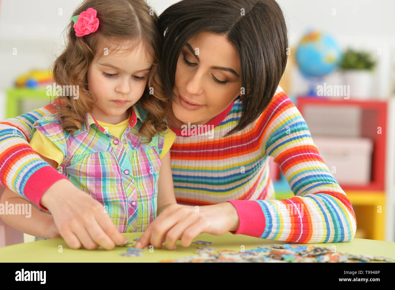 Beautiful young mother playing with her cute little daughter - Stock Image