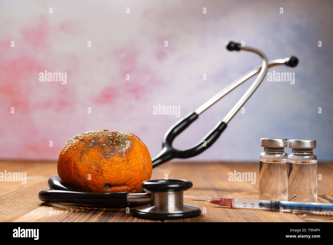 rotten orange surrounded by stethoscope with syringe and bottles of vaccine nearby - Stock Image