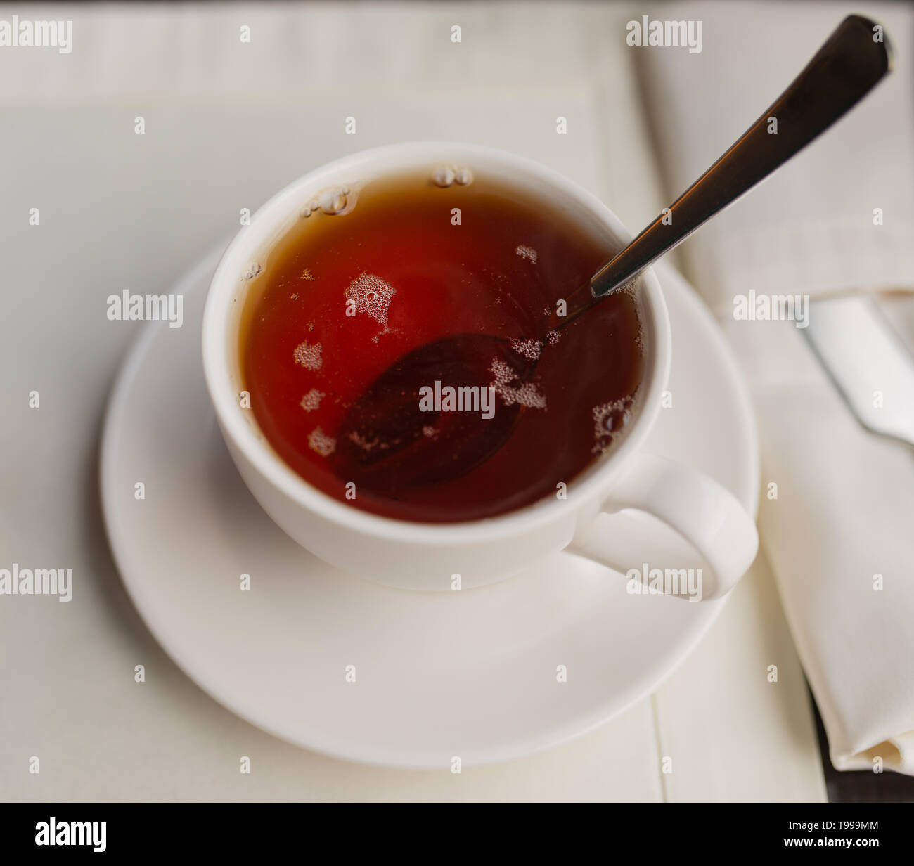 Cup of black tea on a table in a cafe. Selective focus. - Stock Image