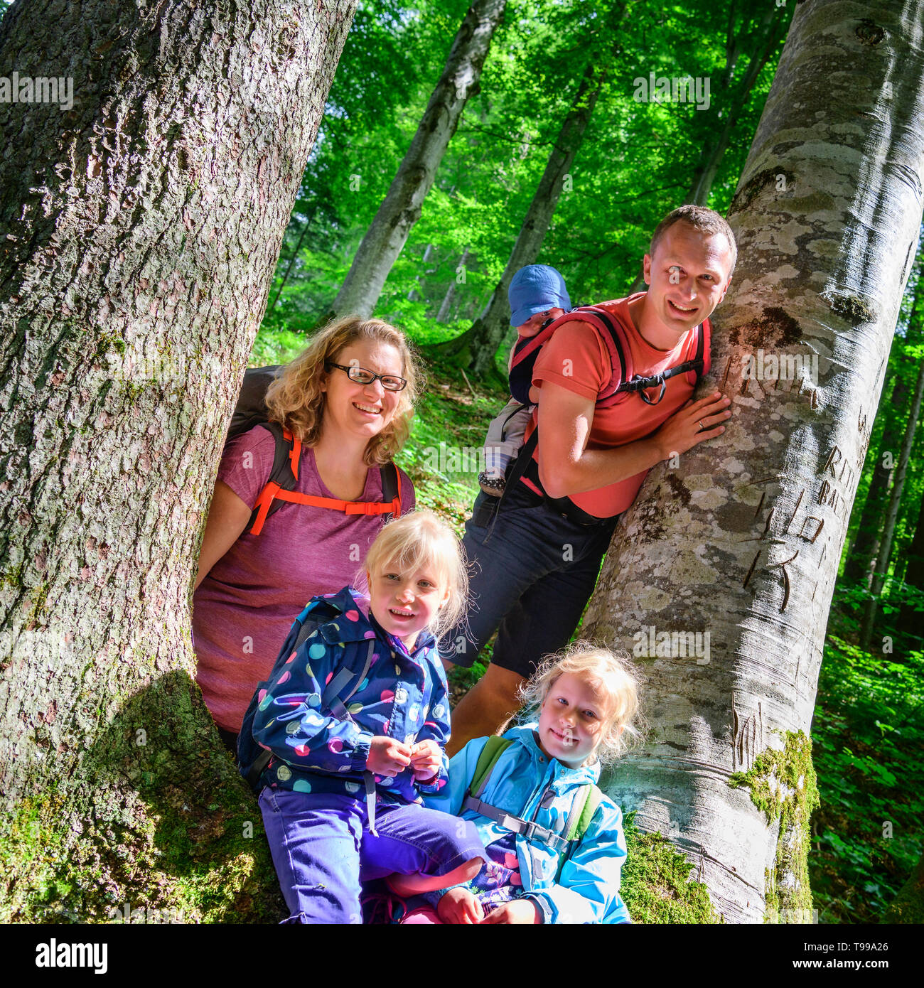 Hiking tour with the hole family around Gerstruben in Upper Allgäu, family posing together between two trees - Stock Image