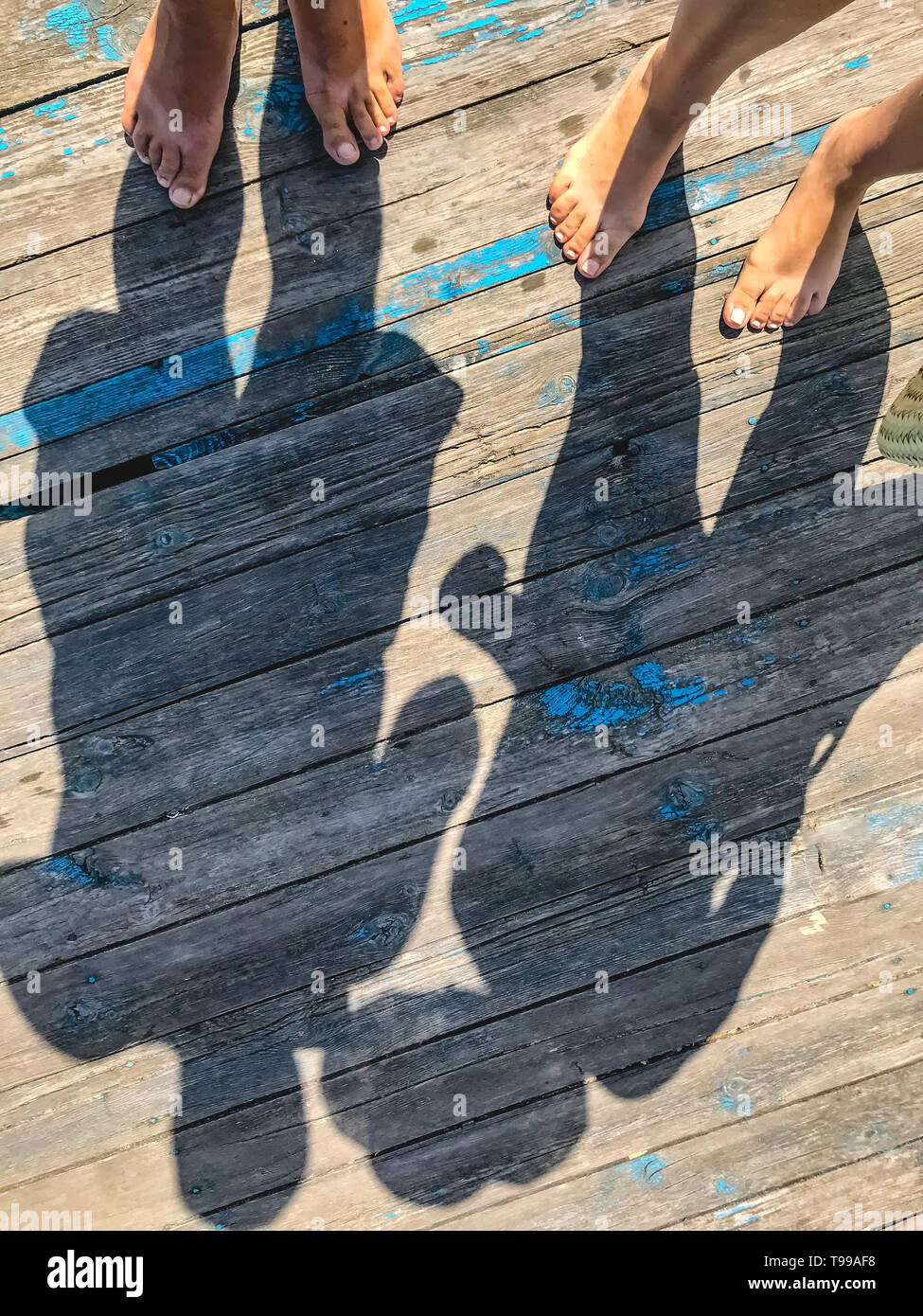 Top view, photo of bare feet and a pair of shadows on a wooden old floor. Photos on vacation, beach, summer. - Stock Image