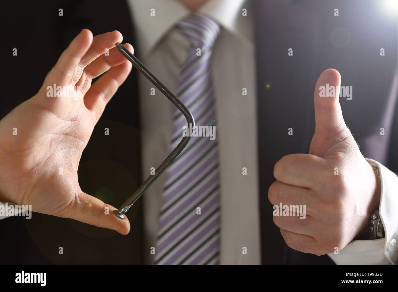 Man in suit and tie bend nail with arms closeup Stock Photo