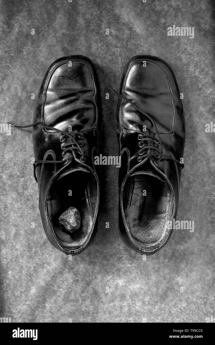 a large stone in the left shoe, black and white - Stock Image