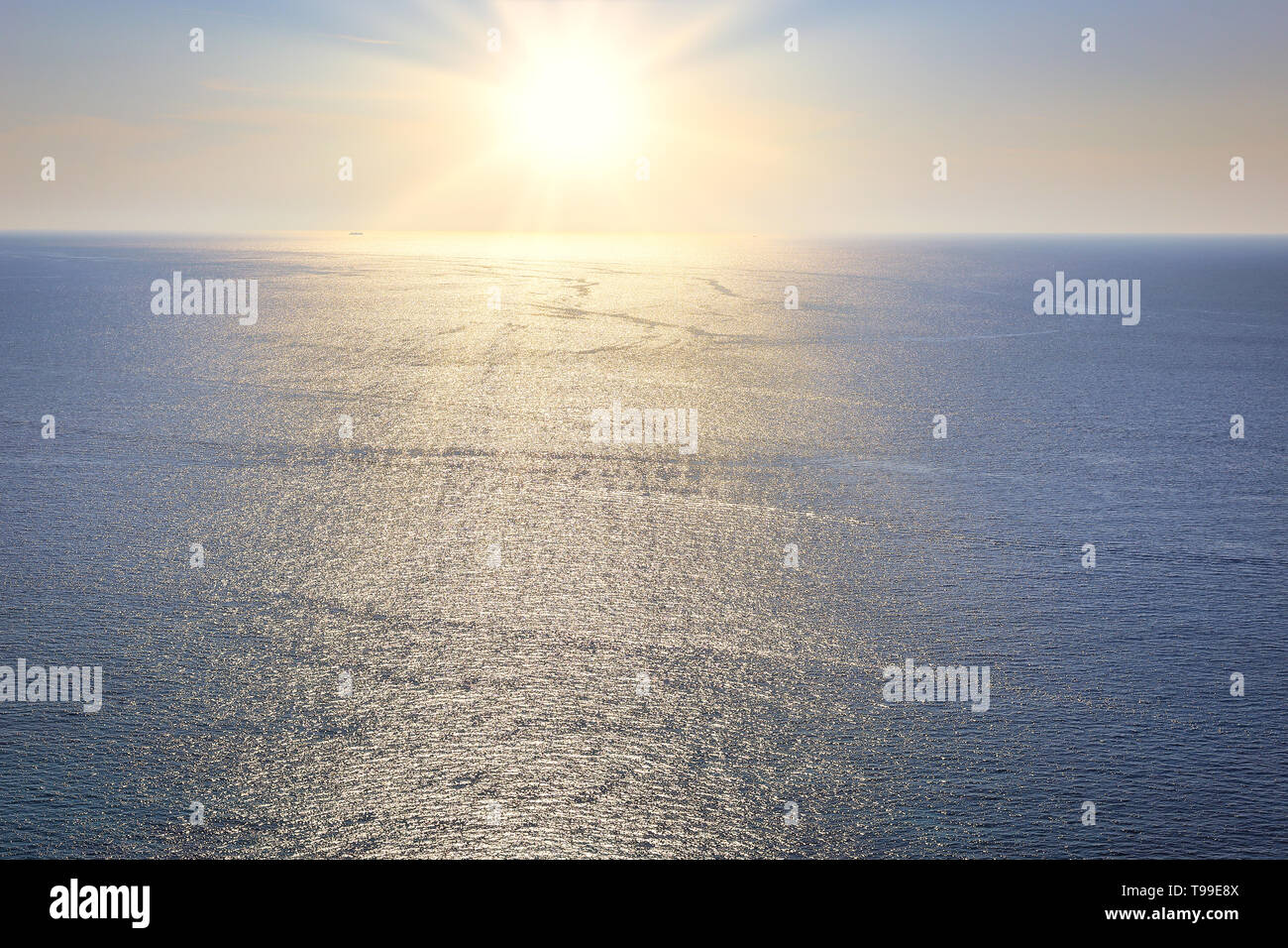 The brilliant sun shines and reflect on the water surface above the sea - Stock Image