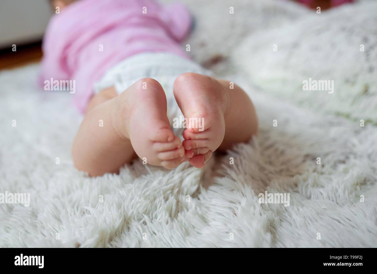 Newborn Baby feet - baby's legs, feet of a newborn baby. - Stock Image