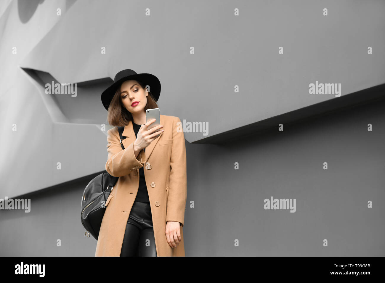 Beautiful fashionable woman with mobile phone near grey wall outdoors - Stock Image