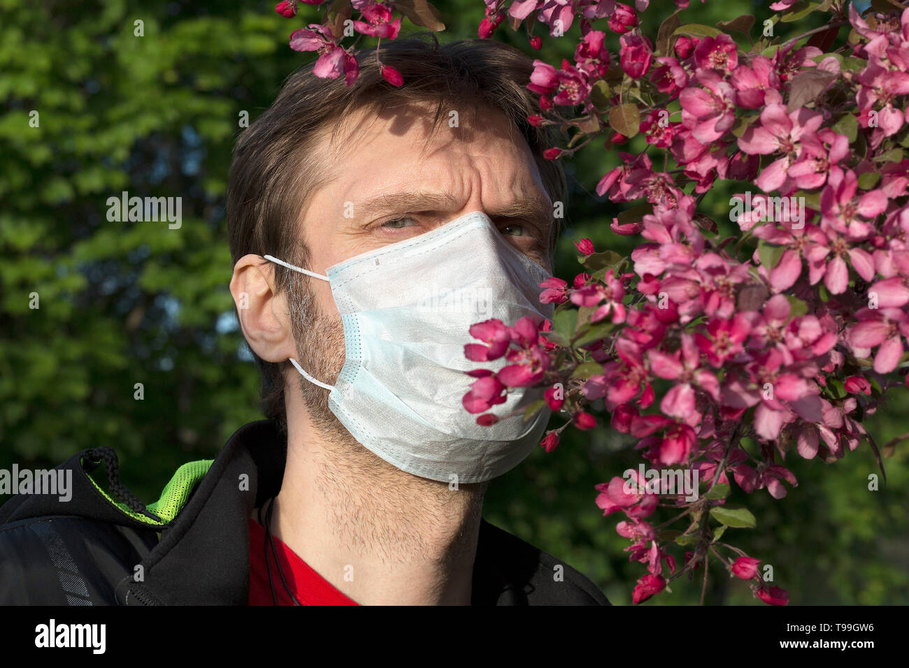 Man wearing a medical mask. Seasonal allergic reaction to pollen - Stock Image