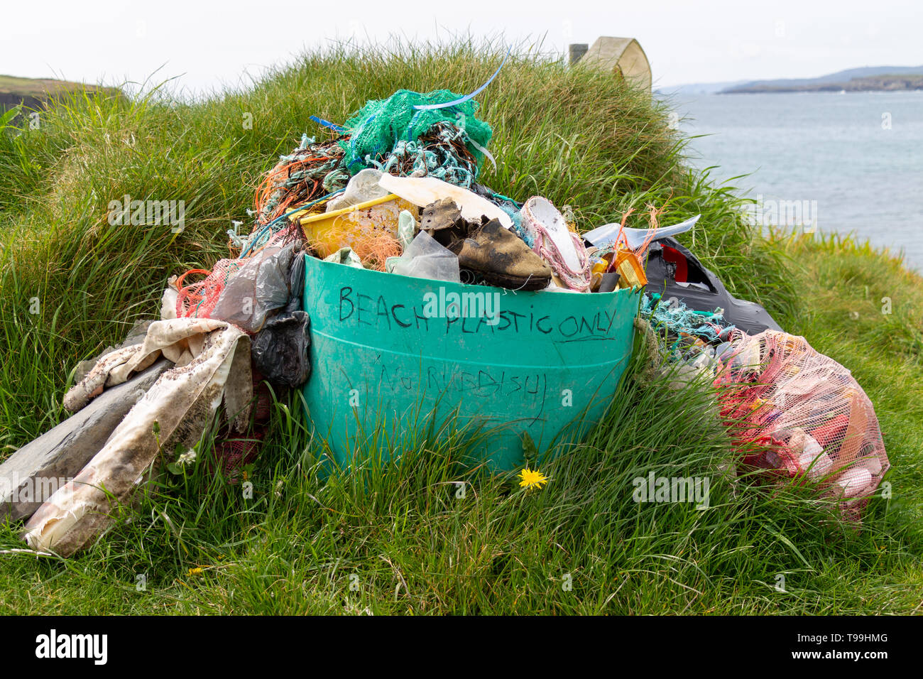 Bin full of plastic pollution collected from the beach - Stock Image