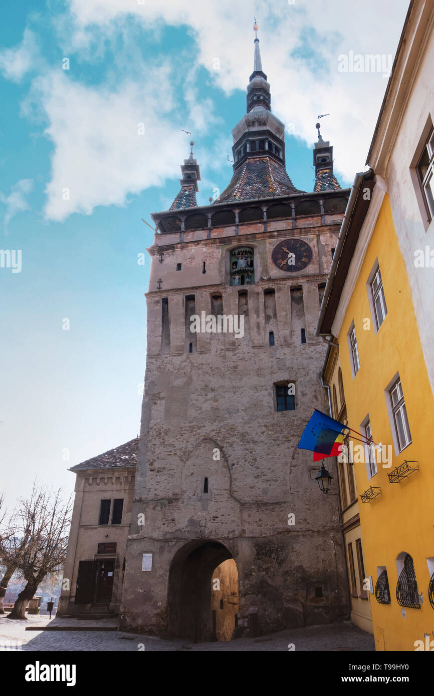Wide view of the Clock Tower in Sighisoara, on a sunny day in spring, against a bright blue sky. - Stock Image