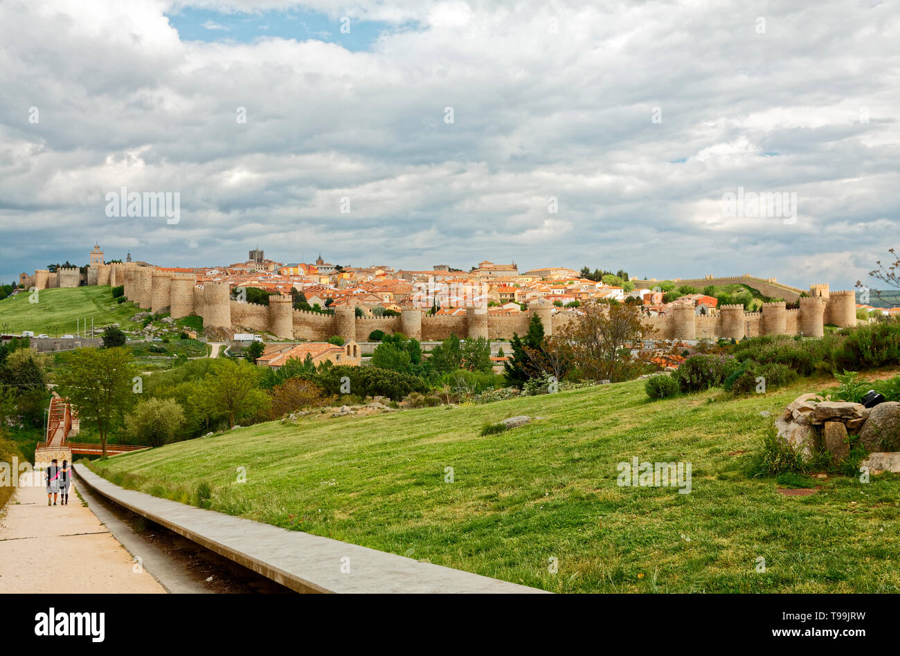 walled city; medieval; distant view; semicircular towers; tiled roofs, couple walking, landscape, Europe; Avila; Spain; spring; horizontal - Stock Image