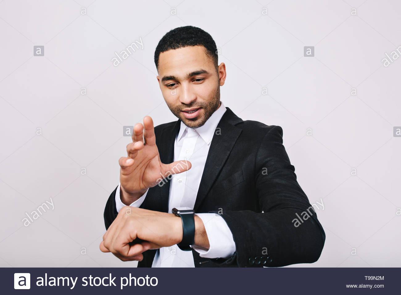 Portrait stylish young man in white shirt, black jacket having fun with watch on white background. Magic time, smart worker, successful businessman, meeting, work, joy - Stock Image