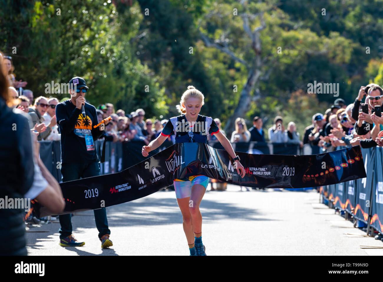 Blue Mountains, Australia - April 16 2019: Ultra-Trail Australia UTA11 race. Runner Paige Penrose, winner of the womens event, crosses the finish tape - Stock Image