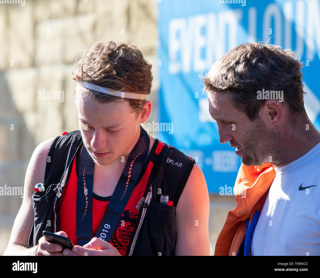 Blue Mountains, Australia - April 16 2019: Ultra-Trail Australia UTA11 race. Runner Will Atkinson, runner up, checking the race statistics at the fini - Stock Image
