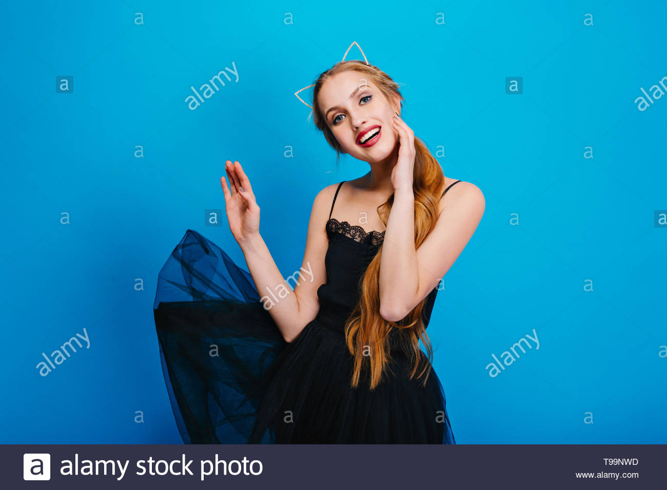 Young pretty woman with beautiful smile, fluttering black dress, posing on blue background. She has long hair, wearing headband with cat ears, nice make up with red lipstick. - Stock Image