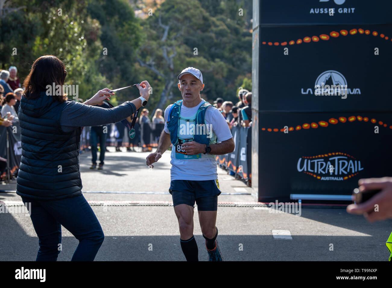 Blue Mountains, Australia - April 16 2019: Ultra-Trail Australia UTA11 race. Runner Tim Lovettat the finish line receiving participation medal. - Stock Image