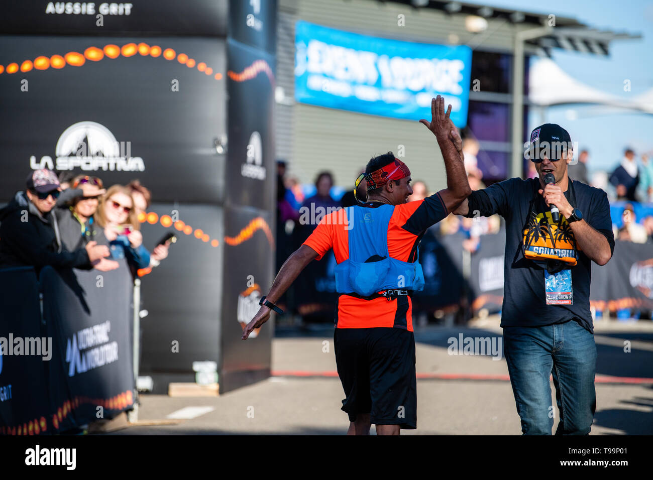 Blue Mountains, Australia - April 16 2019: Ultra-Trail Australia UTA11 race. Runner about to finish on home stretch high fives the comentator - Stock Image