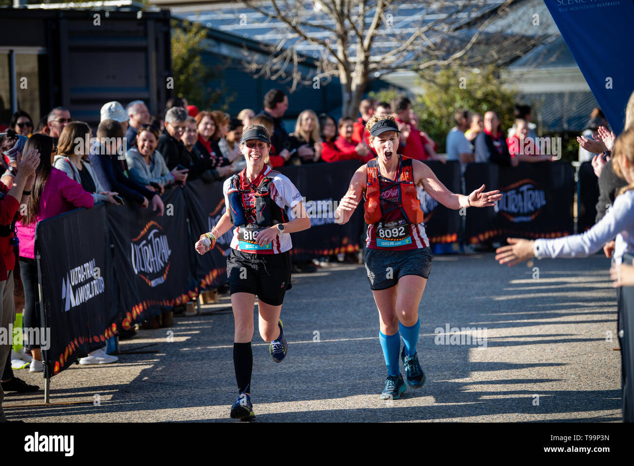 Blue Mountains, Australia - April 16 2019: Ultra-Trail Australia UTA11 race. Runners about to finish on home stretch wave at crowd. - Stock Image
